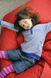 Young girl lying on beanbag