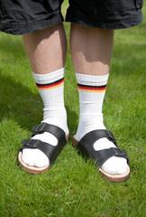 Männerbeine mit Socken und Sandalen