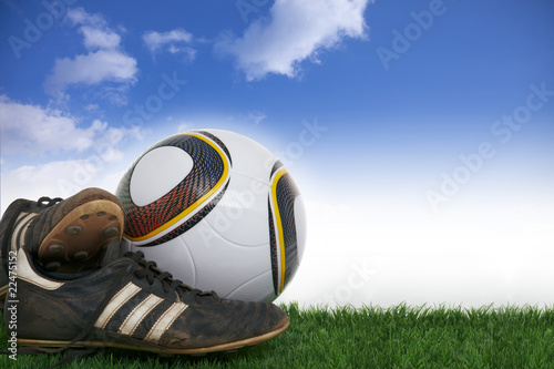 Pair soccer shoes and football on grass in front of blue sky