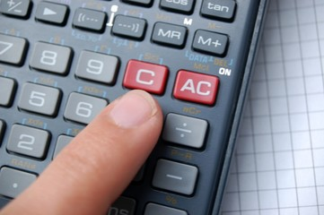 Finger auf Taschenrechner