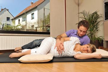 Schwangere Frau und werdender Vater bei Entspannungsübung