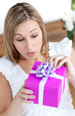 Surprised woman opening a gift sitting on the floor