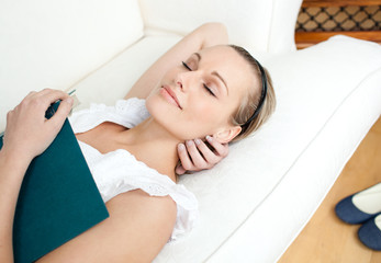 Tired woman sleeping while reading a book