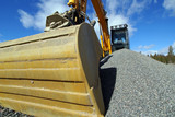 Hydraulic excavator at work. Shovel bucket against blue sky. poster