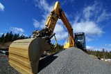 Hydraulic excavator at work. Shovel bucket against blue sky.. poster