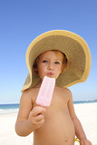 summer vacation: child eating icecream on the beach