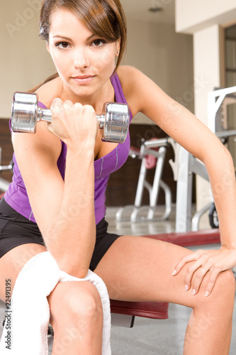 Young woming lifting a dumbbell