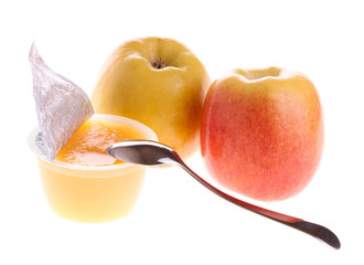 Apple sauce with spoon and two fresh apples