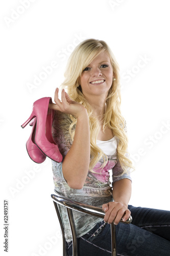 Girl on chair holding pink shoes