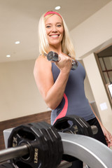 Blonde woman with a dumbbell