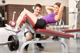 Girl  working on abs with assistant poster