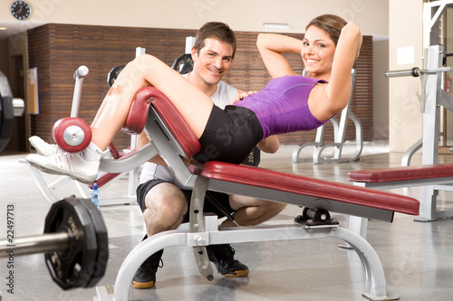 Girl  working on abs with assistant