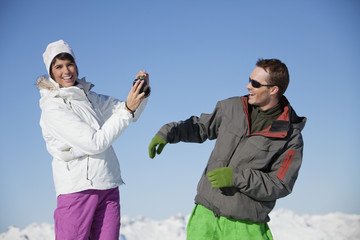 Young woman in ski wear taking a photo of her boyfriend