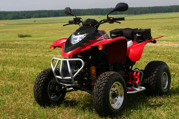 Red quad bike (ATV)  on green field.