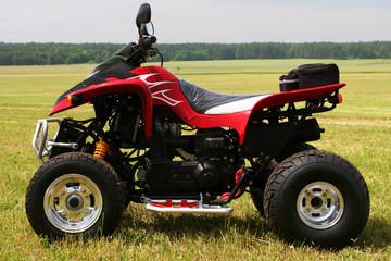 Red quad bike (ATV)  on green field.