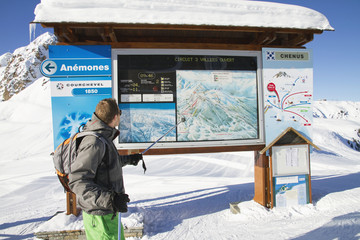 Male skier looking at map, Courchevel, France