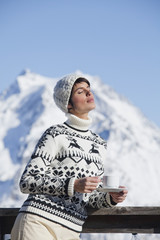 Young woman with coffee cup, enjoying winter sun, mountains in background