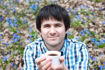 Smiling man drinking coffee on nature