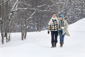 Young couple embracing, walking in snow