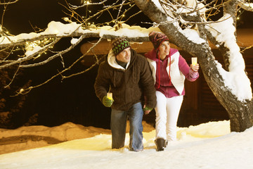 Young couple holding candles, walking in snow by night