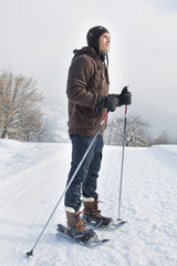 Young man wearing snowshoes
