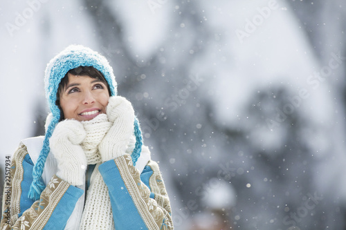 Young woman in winter clothes looking up