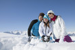 Couple and daughter in ski wear sitting in snow