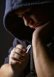 Hooded man holding a razorblade to the scar on his arm poster