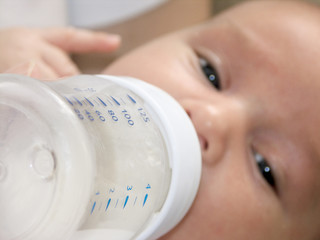 Baby Feeding from infantile feeding-bottle with milk