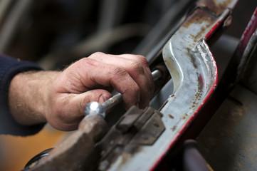 Mechanic Removing Old Car Door In His Garage