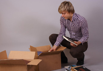 young man moving and packing things and books