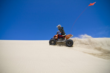 Large sand spray from ATV quadbike rider in the dunes