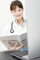 portrait of a young caucasian woman doctor with laptop