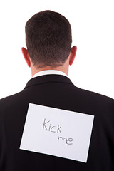 back of businessman, with kick me written in a paper