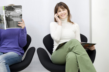 two women sitting in the waiting room for doctors