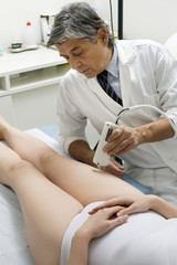 woman receiving laser treatment at the leg from a male doctor