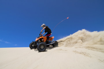 Teen male ATV rider spraying fine sand in the dunes
