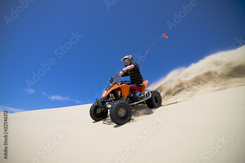 Big sand spray from ATV quadbike rider in the dunes