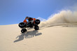 Male riding ATV tipped on 2 wheels sand dune in Oregon.