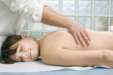 young caucasian woman lying down receiving back massage