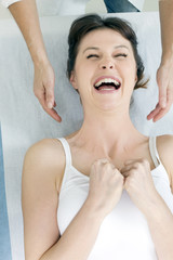 woman lying down smiling and receiving head massage
