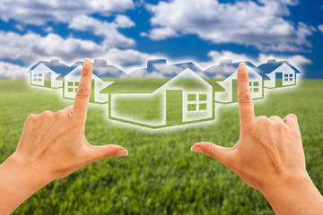 Female Hands Framing Houses Over Grass and Sky
