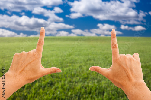 Female Hands Making a Frame Over Grass and Sky