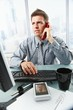 Businessman talking on landline phone in office