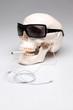 Rauchende Totenkopf mit Sonnenbrille und Ohrhörern hört Musik