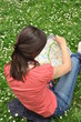 adventure girl with a map of the city siting on the grass