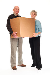 Senior couple carrying home moving box