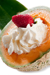 strawberry over whipped cream on open melon