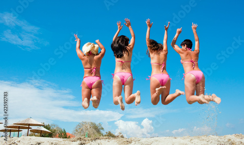 four girls jumping on the beach