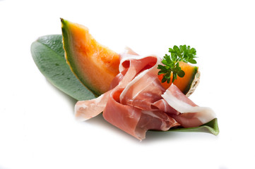 slice of parma ham with melon on white